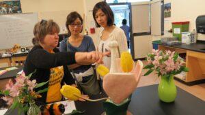 Biology Instructor Nancy Lane shows a pistol to visitors on a large flower model.