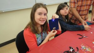 Middle school student makes first sewable circuit with conductive thread and LED.