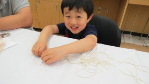 Three-year-old boy works with string to make a parachute model.