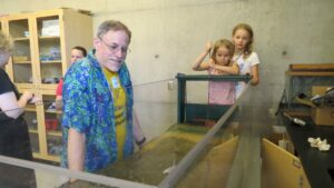 Assistant Dean Kent Short looks on as two sisters work the wave tank.