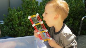 Four-year-old boy blows bubbles with self-made Zometool structure.
