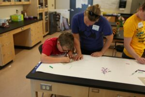 Young boy works with Biology Instructor Heidi Richter.
