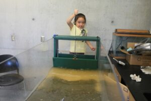 Enthusiastic young visitor making waves in our wave tank.
