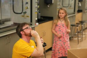 Physics Instructor Caleb Teel shows girl Bernoulli's principle with a straw and ping pong ball.