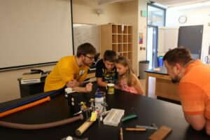 Physics instructor Caleb Teel shows elementary students a demo while father looks on