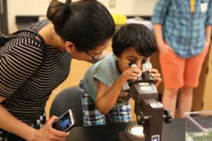 Young child looking through microscope with mom looking on