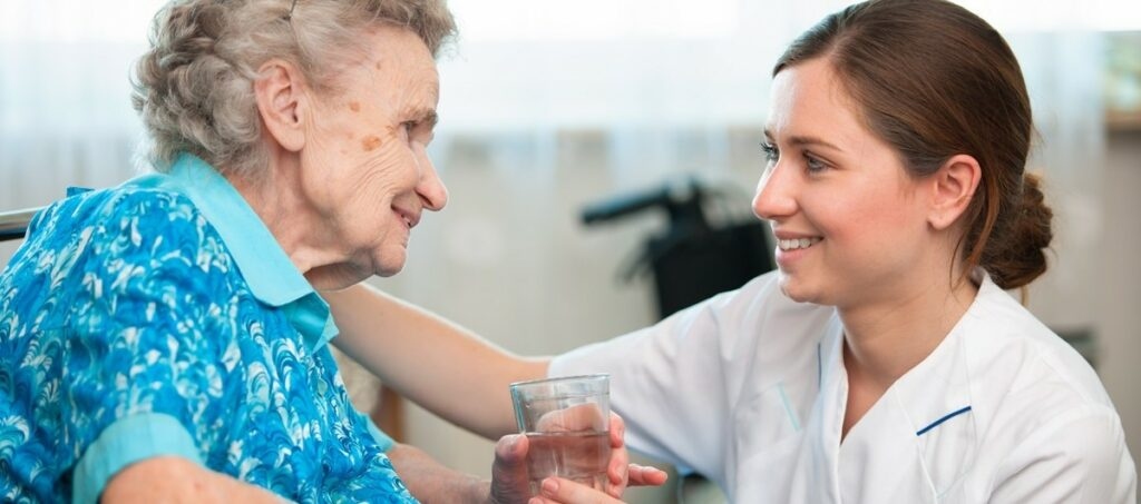 Picture of elderly woman being cared for by a certified nursing assistant.