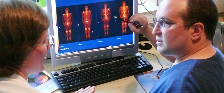 Picture of Nuclear Medicine Instructor and student looking at patient data on computer.