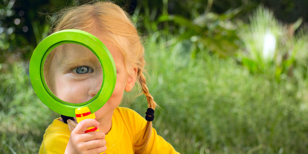 Picture of little girl holding a magnifying glass to her eye.