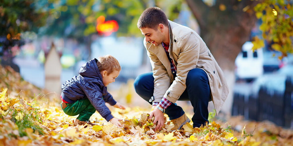 Picture of father and son having fun in autumn park