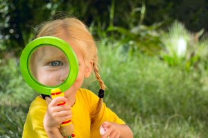 Picture of girl holding magnifying glass to her eye.