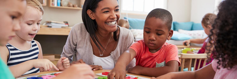 teacher smiling while children play