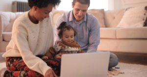 parents and infant in front of laptop