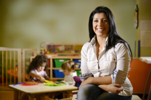 Picture of happy teacher with children eating in kindergarten