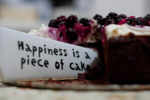 "Photo of cake being cut into with a knife that says, ""happiness is a piece of cake"""