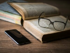 photo of a wood desk with glasses on top of a book, next to a smart phone