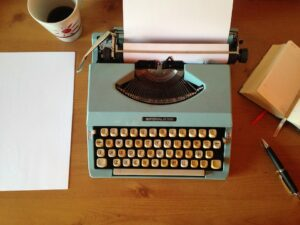 typewriting on wooden desk with book, coffee, and piece of paper