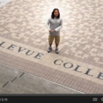 Screenshot from Music Video showing man standing in Bellevue College courtyard