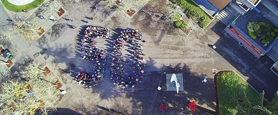 Students, faculty and staff spell out a giant 50 in the courtyard
