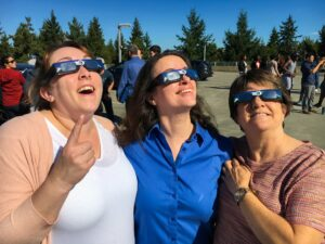 Three faculty members other look up at the solar eclipse.