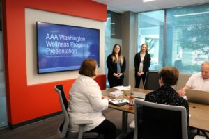 Two students stand in front of a projection screen in a meeting room