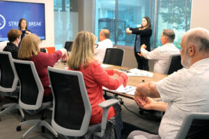 Two BC students demonstrate a wellness exercise to a group in a meeting room