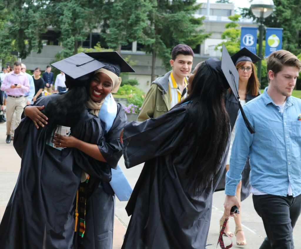 Students laugh and hug prior to the graduation ceremony