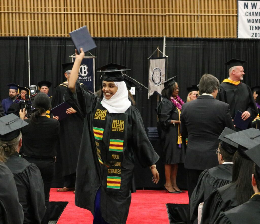 A student waves her diploma during the graduation ceremony