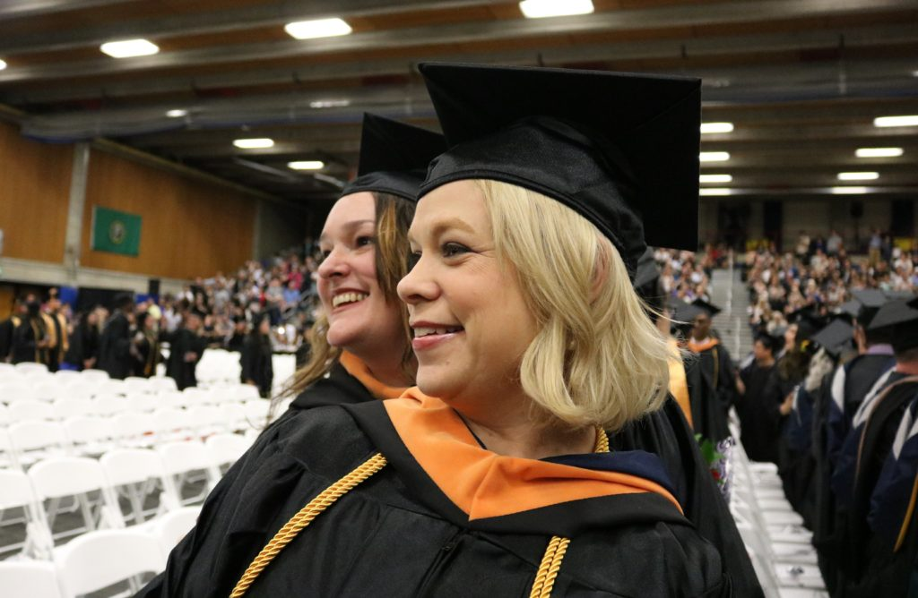 Two women smile during the graduation ceremony