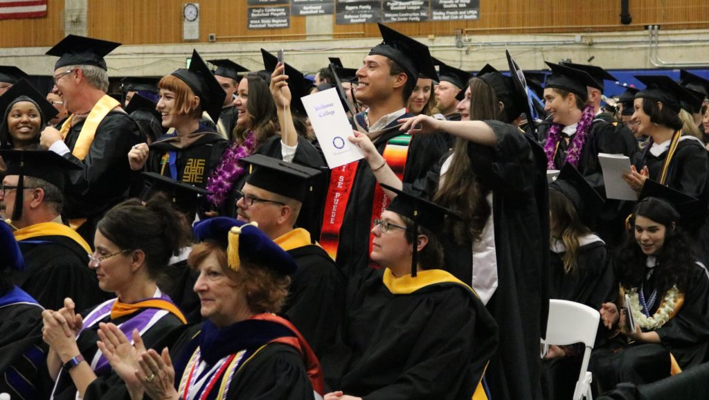 students cheer for friend during graduation ceremony