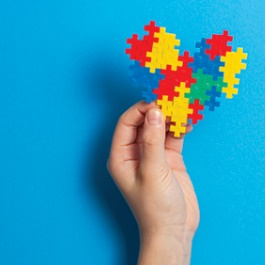 A hand holding colored blocks in shape of a heart