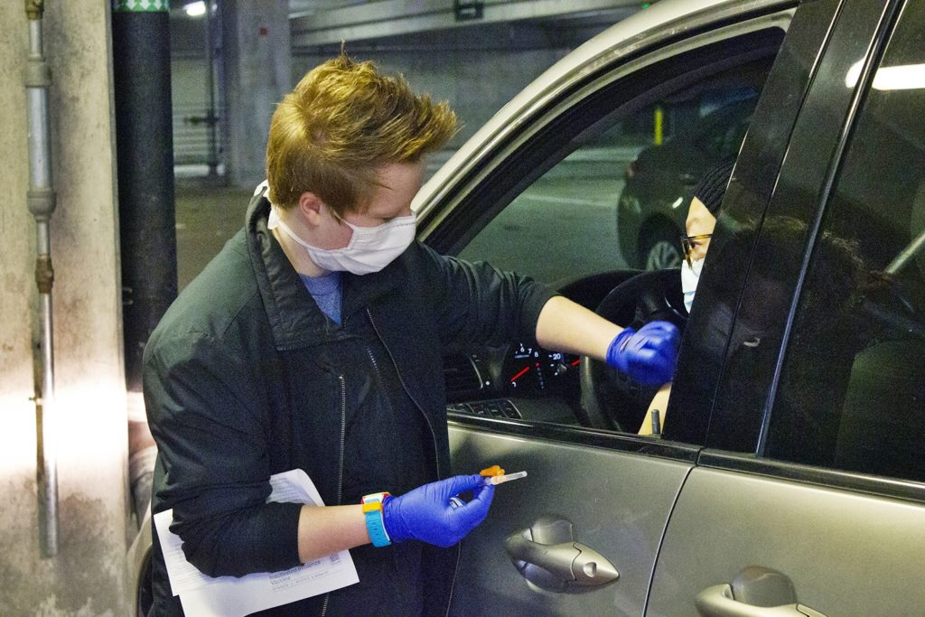 A masked nurse gets ready to deliver a flu vaccine at the drive-thru flu shot clinic