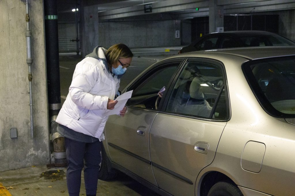 A nurse gathers information from a flu shot recipient