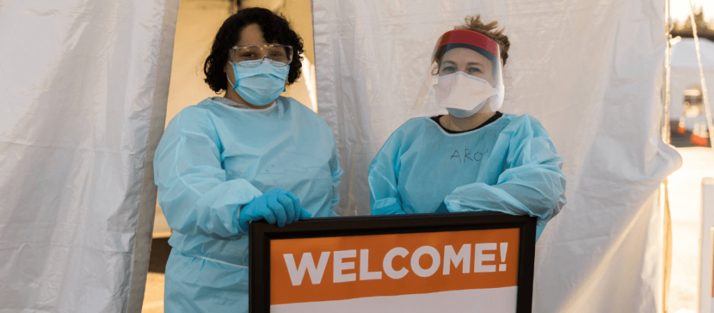 Nurses in scrubs and masks stand by a welcome sign