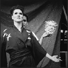 Black & White, lady with kimono, man standing behind her holding a mask