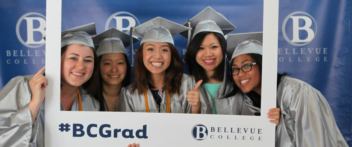 group of five bc students wearing graduation cap and gowns smiling for a picture and holding a picture frame prop
