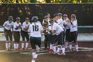 BC Women's softball team gathers to welcome player 18 to home plate