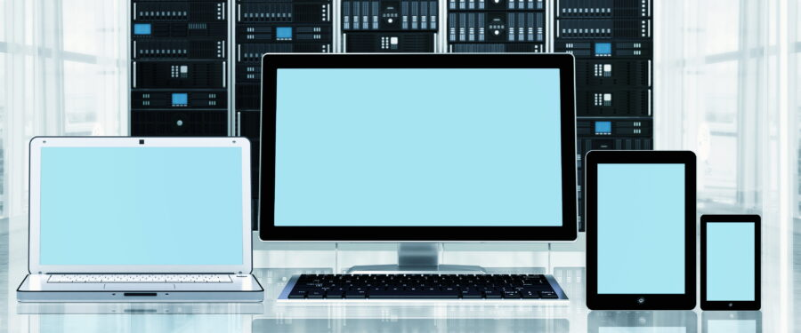A computer, laptop, tablet, and a smart phone in front of server cabinet