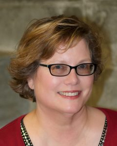 headshot of white female presenting person with short brown hair and black glasses