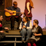 Entanglement Theory - a group of people singing on the porch while a male character is playing the character