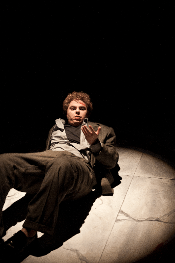 Very Still and Hard to See. Male character lying on stage looking at his hand to see what's on it.