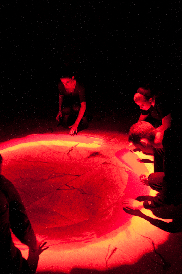 Very Still and Hard to See. characters surrounding a red pool of vapor looking down into it.