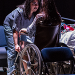 one woman talking to another woman sitting in a wheelchair