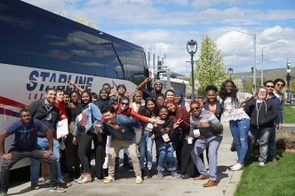 A group of students in front of a bus