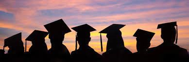 graduates silhouetted against sunset