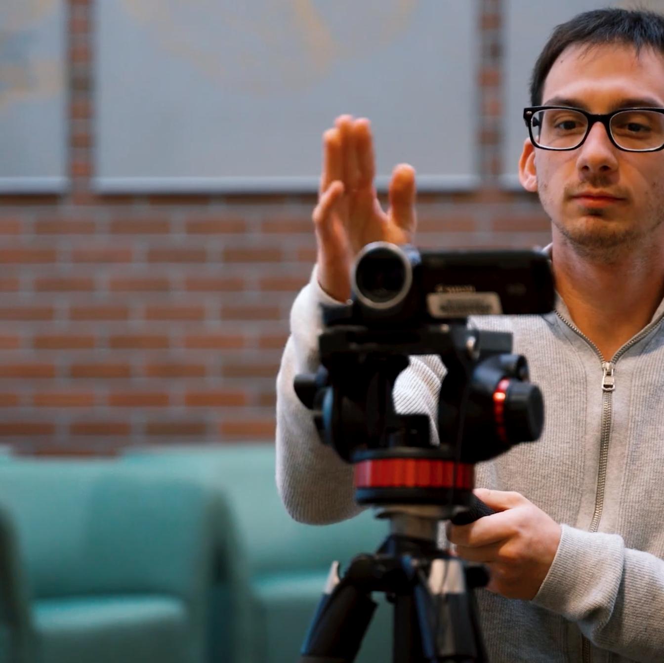 Man behind video camera aligning shot.