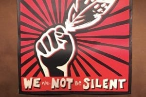A poster featuring a black hand with a feather and radial lines extending from the hand to the edges of the poster. Text reads, We will not be silent, the text is in white