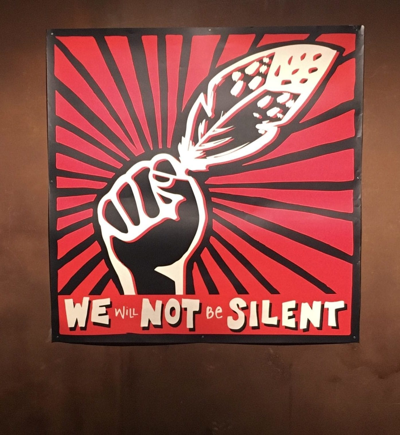 "A black and red poster that features a hand raised in protest, holding a feather towards the top right corner. The hand is black and elements of the feather are black. Extending from the hand and feather in a radial design are black lines of different thicknesses. A black frame extends around the poster. In white the words ""We Will Not Be Silent"" are written on the bottom edge of the poster."