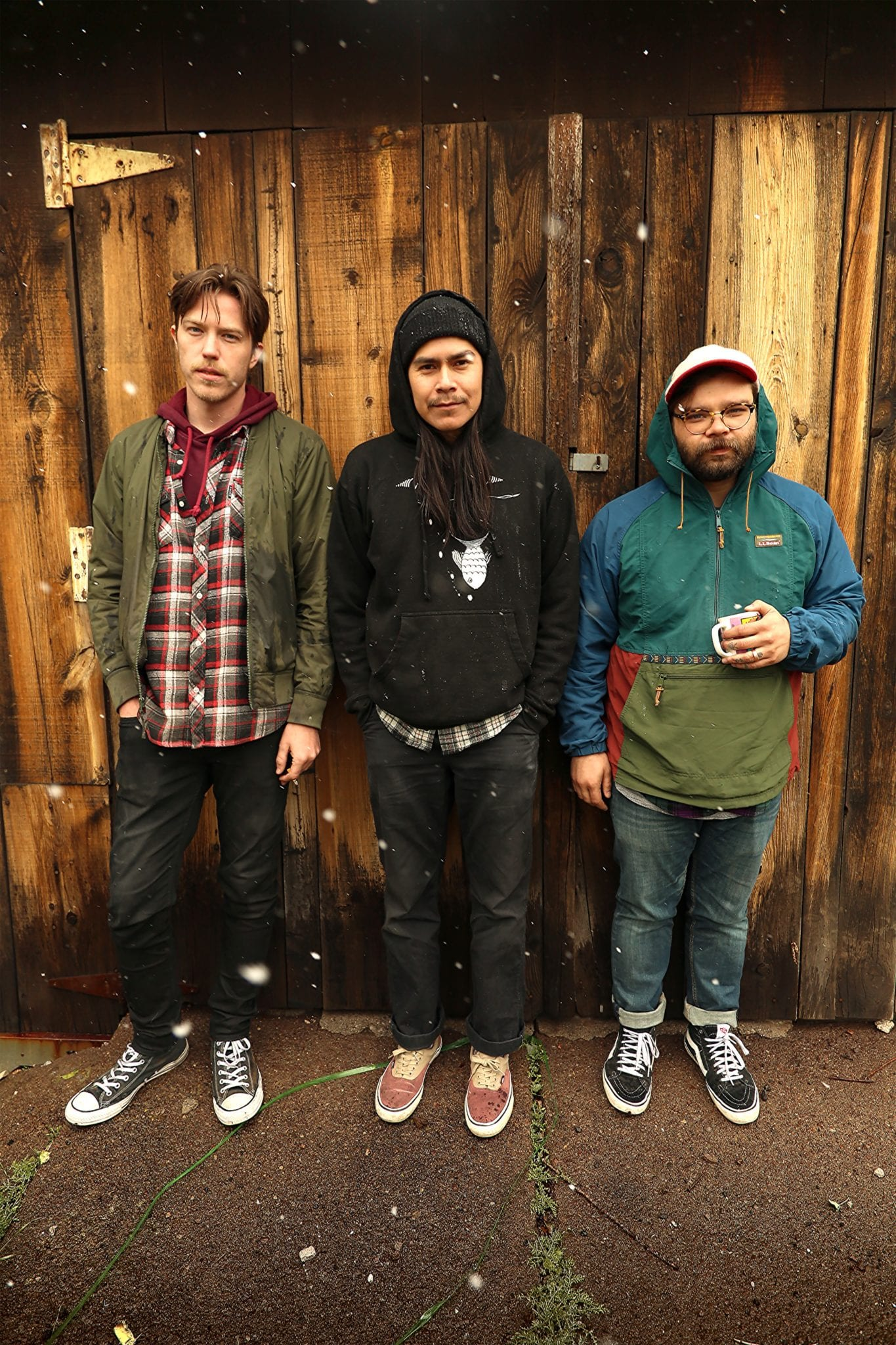 "A photograph of 3 musicians from the band ""The Savages"". They are shown standing in a horizontal row in front of a wood door with white hinges, the hinges have rust on them. Each member of the band is wearing a different outfit. The individual in the center and on the right have hoods up from their sweaters and coats. The member of the band on the left does not have a hood. The individual on the far right is holding a mug.The ground they are standing on is concrete and has small plants growing in a crack."